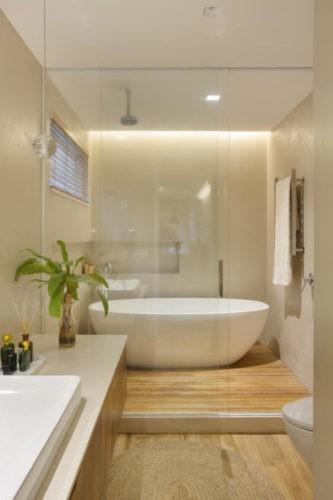 Banheiro com box grande e uma bahheira branca dentro