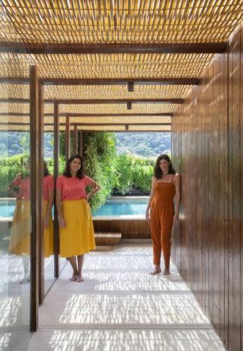 Foto das sócias Carolina Escada e Patricia Landau, da Escala Arquitetura., em um corredor com teto em bambu