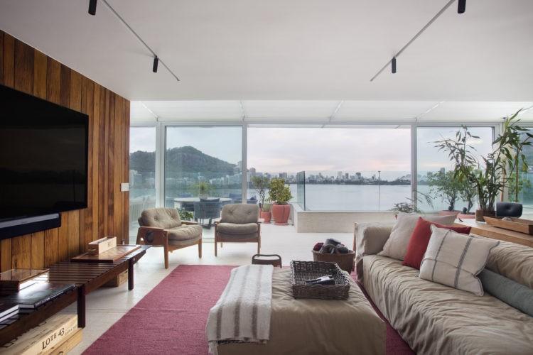 Ampla sala de cobertura, com varanda e vista para a Lagoa. Sofá bege e parede revestida de madeira com tv