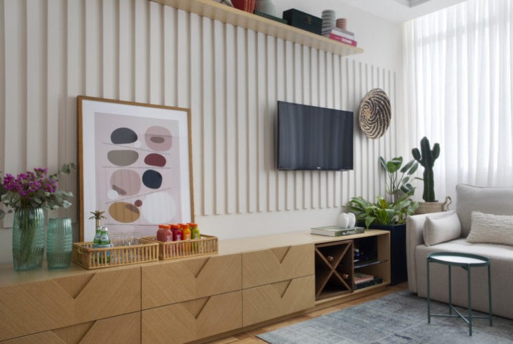 Parede de sala com ripas de mdf pintdas de branco, rack baixo em mdeira ao longo da parede