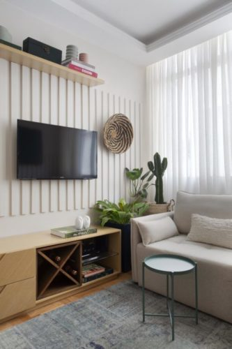 Projeto de decoração low cost. Sala com sofá claro, móvel baixo em madeira e tv na parede