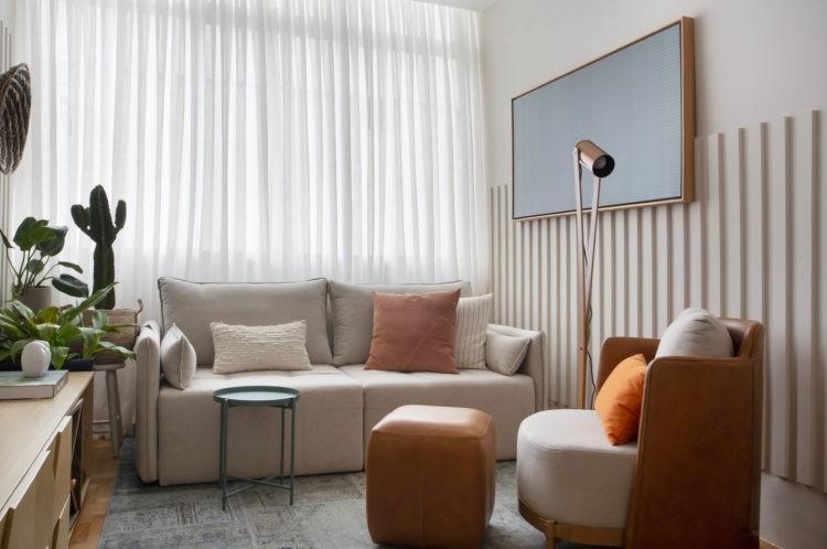 Sala compacta, com cortina de linho branca, sofá bege epuff de coro marrom