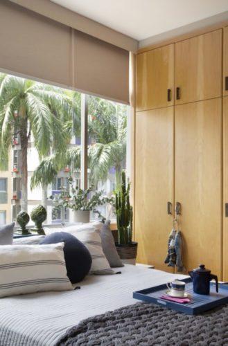 Projeto de decoração low cost. Quarto com armario ao lado da cama com porta em madeira e cama enconstada na janela