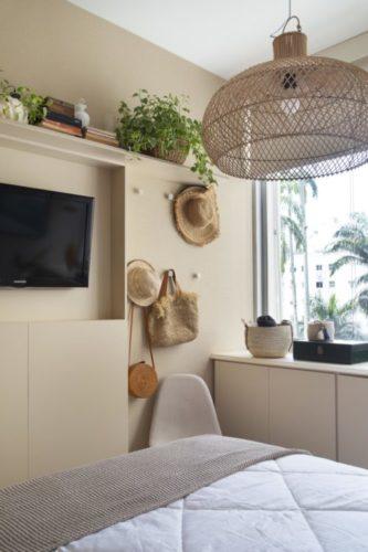 Parede em frente a cama pintada de bege, tv na parede e um movel estreito embaixo pintado da mesma cor que a parede