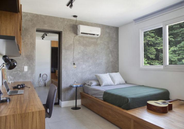 Quarto cm parede cimenticia, cama em tablado de madeira e arvores na vista da janela