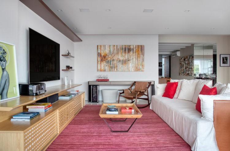 Sala ampla e clara com tapete rosa na fente do sofá branco, rack em madeira baixo e tv em cima