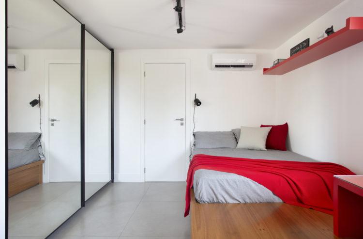 Portas de armaros espelhadas, colchão em cima do tablado em madeira