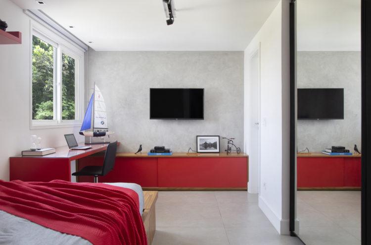 Quarto cm paredes cinzas. movél com portas varemelhos embaixo da tv na parede e bancada de studos vermelha
