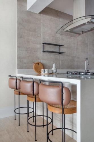 Bancada alta branca na cozinha e tres banquetas em couro e palhinha