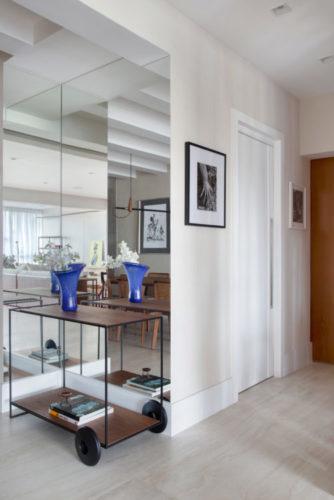 Entrada dp apartamento com parede espelhada e carrinho de chá com vaso azul em cima