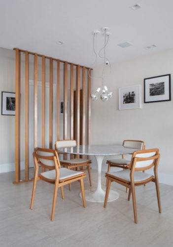 Sala de jantar separada da entrada por painel com ripas de madeira, mesa redonda com tampo de marmore e pés branco, com quatro cadeiras em madeira e tecido cru