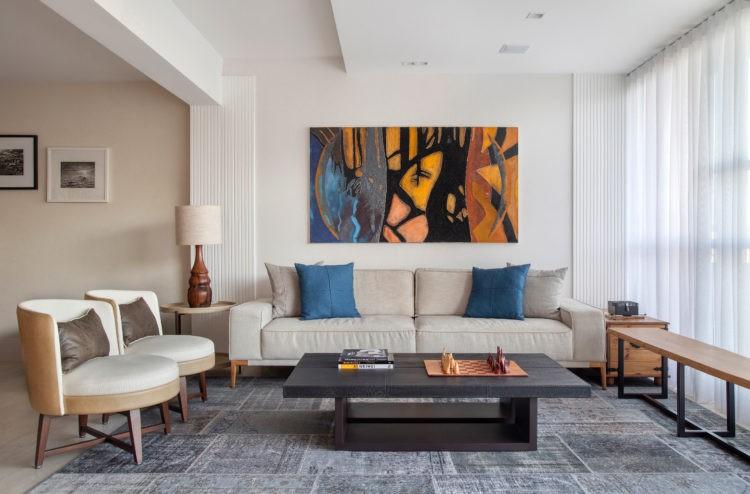 Apartamento de 210m² no Parque Guinle, com vista para o Cristo Redentor. Sala ampla e clara cm sofá bege, tapete azul e um quadro do artista Carlos Vergara