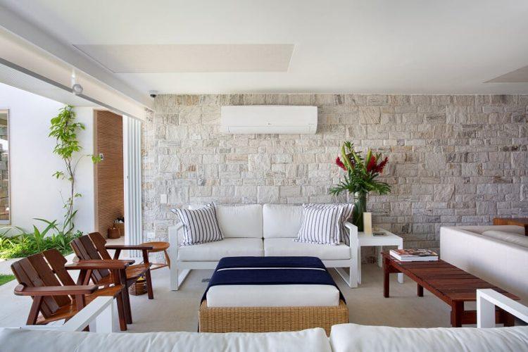 Sala de um casa de praia com parede em pedra, sofá branco e puff de vime em frente