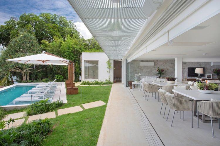 Em Angra, a mais perfeita tradução do paraíso. Casa de praia com varanda com mesas e caderas bege, piscina com ombrelone