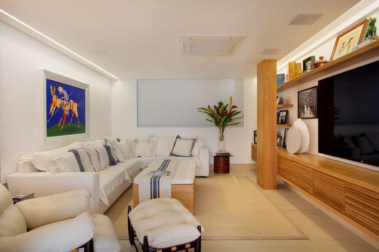 Sala de Tv com um sofá branco grande em L , em frente, um rack baixo em madeira euma TV grande em cima