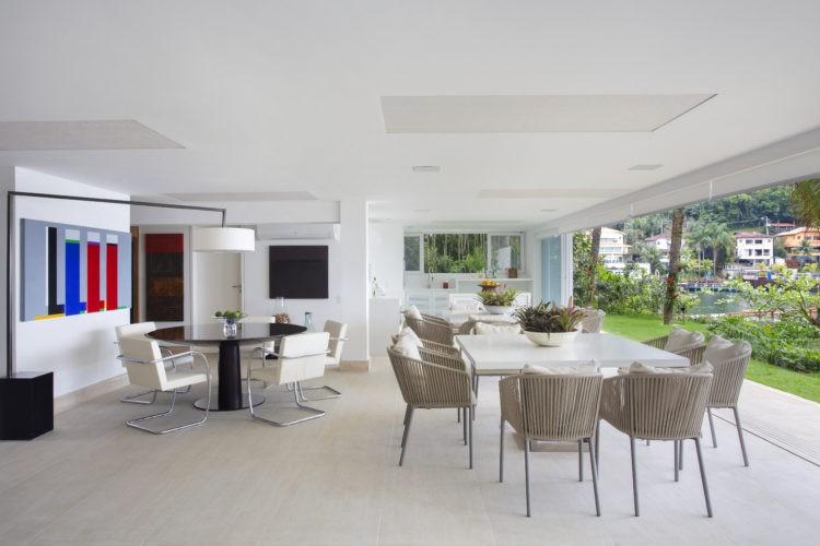Sala de uma casa de prai, clara e aberta para o gramado.Mesa quadrada clara e cadeiras claras