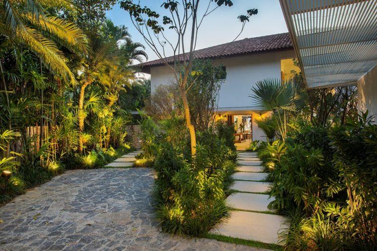 Entarad de uma casa com caminho de pedra e paisagismo tropical, alemiras e plantas