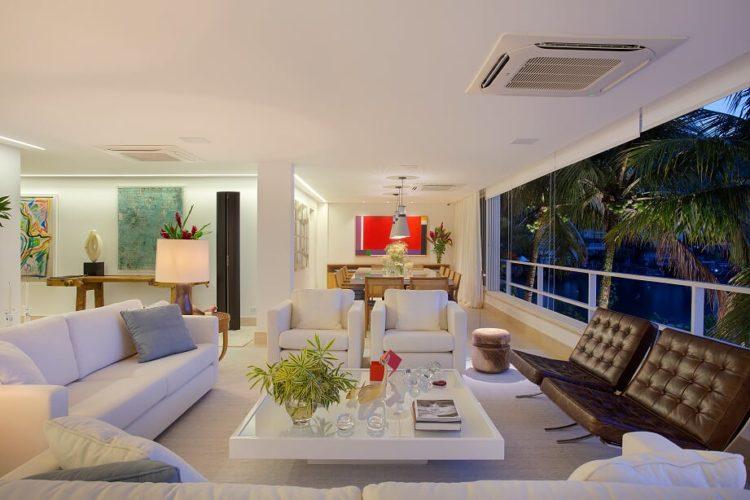 Sala clara em uma casa de praia, janelas com vão grande , sofá branco e duas poltronas em couro marrom