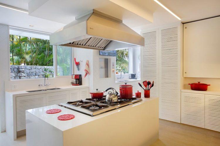 Cozinha toda branca, mobiliario e bancadas, ilha no centro com fogão embutido e coifa em cima