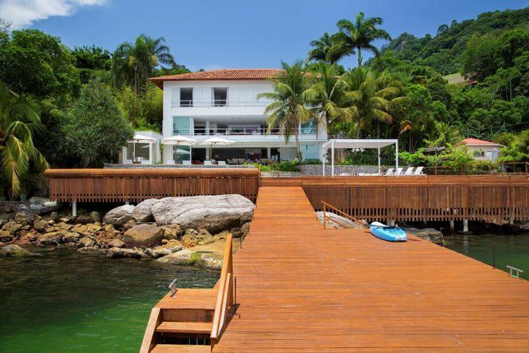 Em Angra, a mais perfeita tradução do paraíso.Casa na costa verde, branca com tres andares e um longo deck de madeira na frente