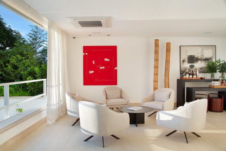 Um quadro vermelho na parede, em frente, um circulo com cinco cadeiras e uma mesa baixa no meio.