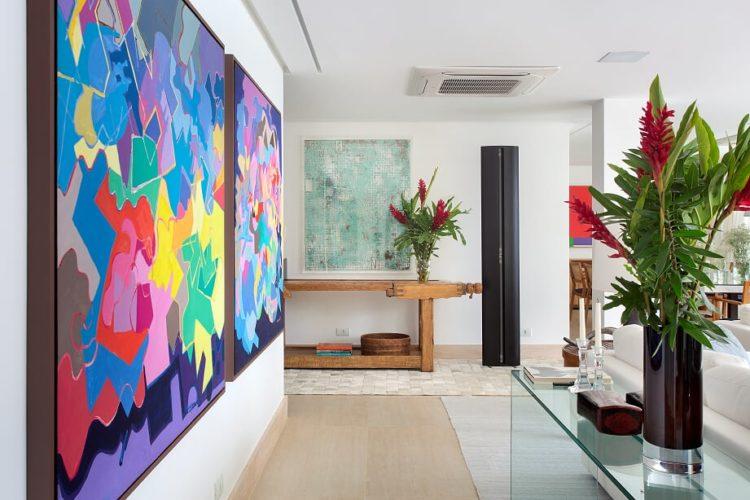 Sala com quadro colorido na parede e em frente aparador de vidro
