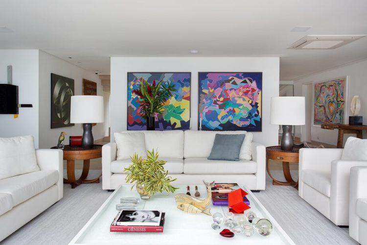 Sala clara na casa de praia, sofás brancos e duas telas bem coloridas ao fundo ao fundo