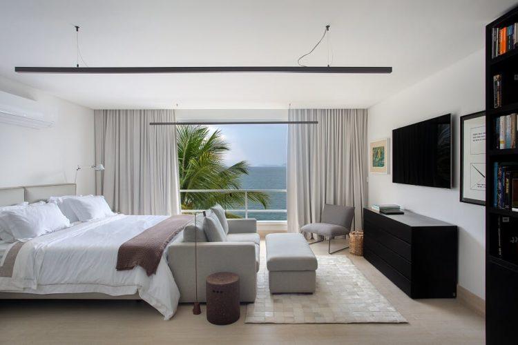 Quarto de casal, cama grande , sofá cinza em frente e de frente para a tv na parede. Sacada aberta com vista para o mar
