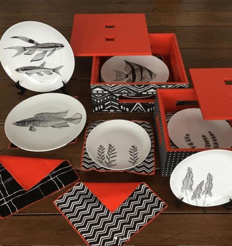Caixa vermelha embalando pratos rasos em porcelana com peixes pintado a mão.