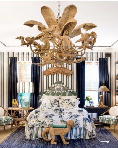 Quarto com as paredes revestidas em tecido listrado de azul e branco, lustre em vime com folhas e bichos, cama estampada