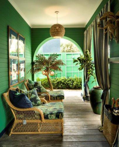 Varanda com as paredes pintadas de verde, duas cadeiras chaise em vime e tecido estampado