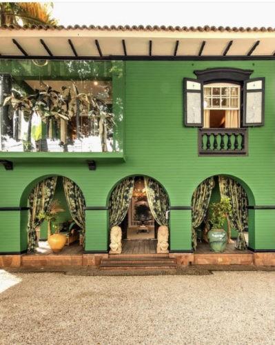 fachada da loja Entreposto, frete toda pintada de verde. tres arcos na entrada com cortinas nas laterias