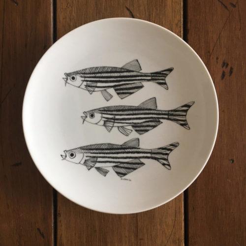 Prato de porcelana redondo com tres peixes pintados na cor preta