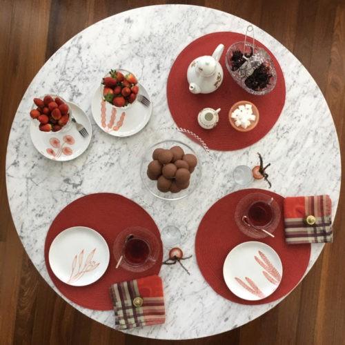 Mesa redonda pota com jogo americano e pratos de porcelana pintados a mão com motivo de alga marinho