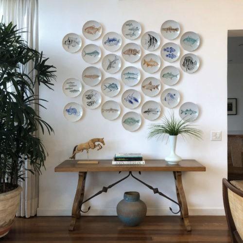 Parede com varios pratos redondos brancos com peixes pintados no meio. Um arranjo de pratos na parede em cima de um aparador de madeira