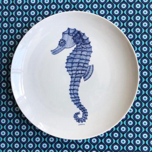 Pedras (e peixes) que encontrei pelo caminho. Prato raso em porcelana branca com um cavalo marinho na cor azul pintado a mão