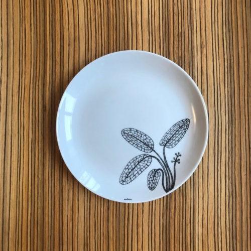 Prato de sobremesa em porcelana com desenho de algas em preto no canto e pintado a mão.