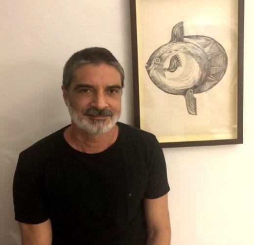 Foto do artista Gustavo Portela, de camiseta preta e barba