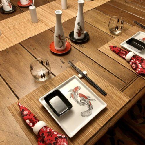 Mesa posta com louça em porcelana pintada a mão com motivo de carpas
