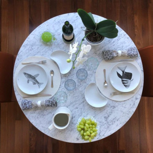 Mesa redonda posta com jogo americano branco e pratos redondos com peixes pintados a mão