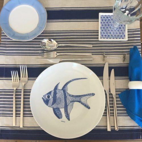 Mesa posta. talheres de prata, prato raso em porcelana com peixe azul pintado a mão no centro