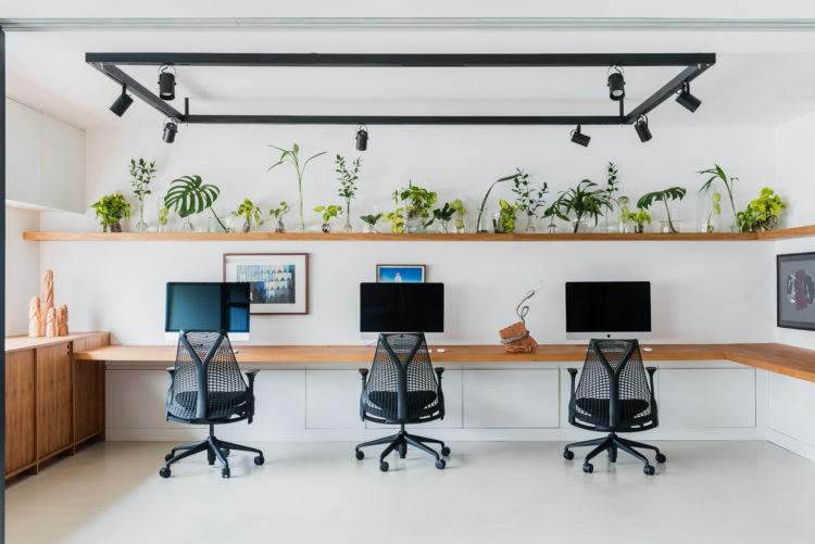 Novas formas de trabalhar, sala clara com prateleira em madeira, trilho preto no teto, tres cadeiras em frente ao computador