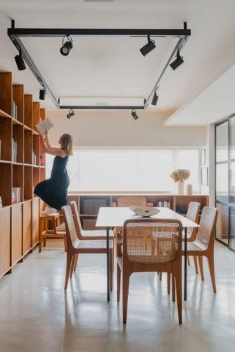 Sala de reunião clara com um janelão, mesa e cadeira em madeira e trilho preto no teto