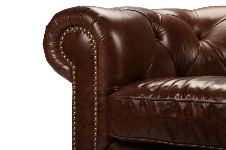 sofá Chesterfield, aquele grande, confortável e capitonê (ou botonê, cheio de botõezinhos),, marrom em curo e braços arredondados com tachas douradas