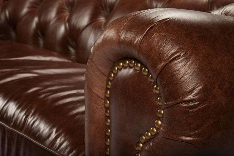 sofá Chesterfield, aquele grande, confortável e capitonê (ou botonê, cheio de botõezinhos), em couro marrom e braços arredondados com tachas