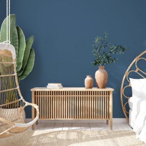 Parede Azul e na frente um balanço suspendo em fibra natural e uma comoda de madeira com arranjo verde em cima