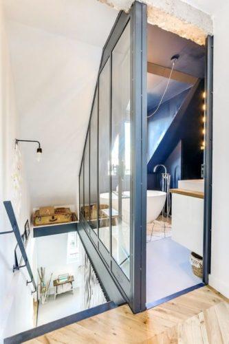 Escada que da acesso ao banheiro com banheira e uma janela. Esquadrias azuis