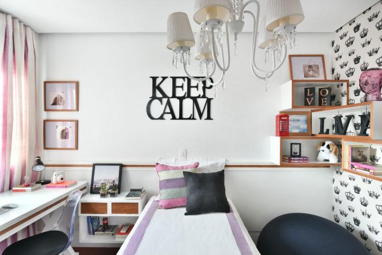 Quarto de adolescente rosa e preto na decoração, e em cima da cama em escultura em madeira pintada de preto, escrito em ingles keep calm
