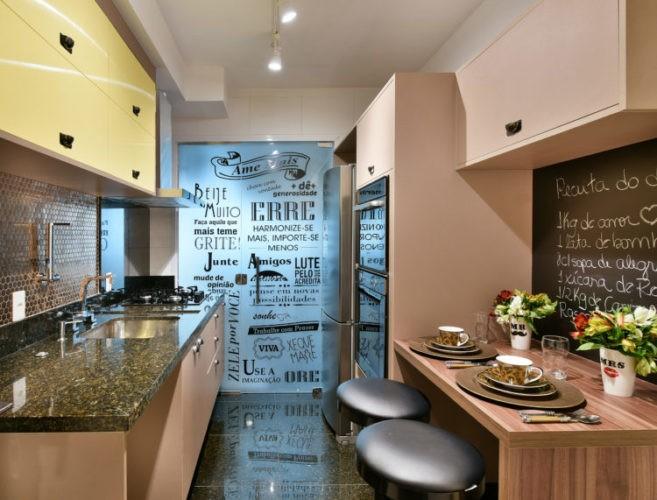 Cozinha com planta retangular, de um lado bancada e de outro mesa enconstada na parede revestida com lousa e escrito uma receita
