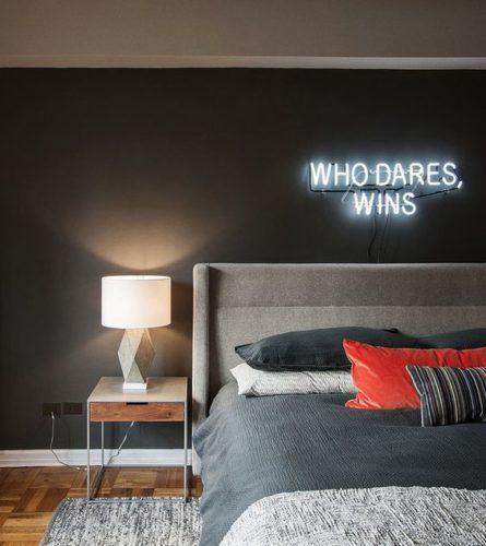 Quarto de casal, com parede pintada na cor cinza escuro e um neon aplicado em cima da cama. No neon a frase em ingles who dares wins